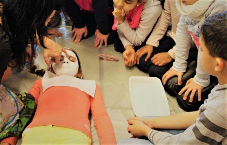 La plasticienne montre la méthode, ensuite chaque enfant fait un masque sur le visage d'un camarade.