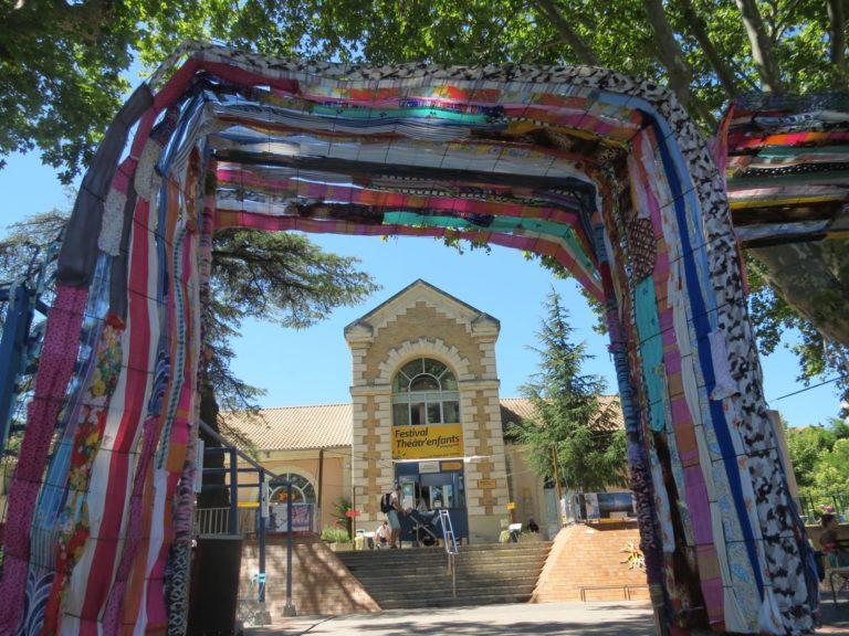 Une porte d'entrée magique qui permet d'aller voir les beaux spectacles présentés par l'Eveil Artistique lors du Festival Théâtre Enfants! Matérialiser cette porte est une tradition, nous l'avons respectée en créant une double entrée avec du grillage tissé de bandes de tissus.