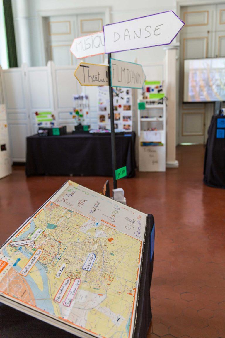 La zone d'orientation avec: - La table d'orientation pour se repérer dans la ville, retrouver les lieux visités et les écoles participantes. - Les grands panneaux signalétiques urbains pour se repérer dans l'expo