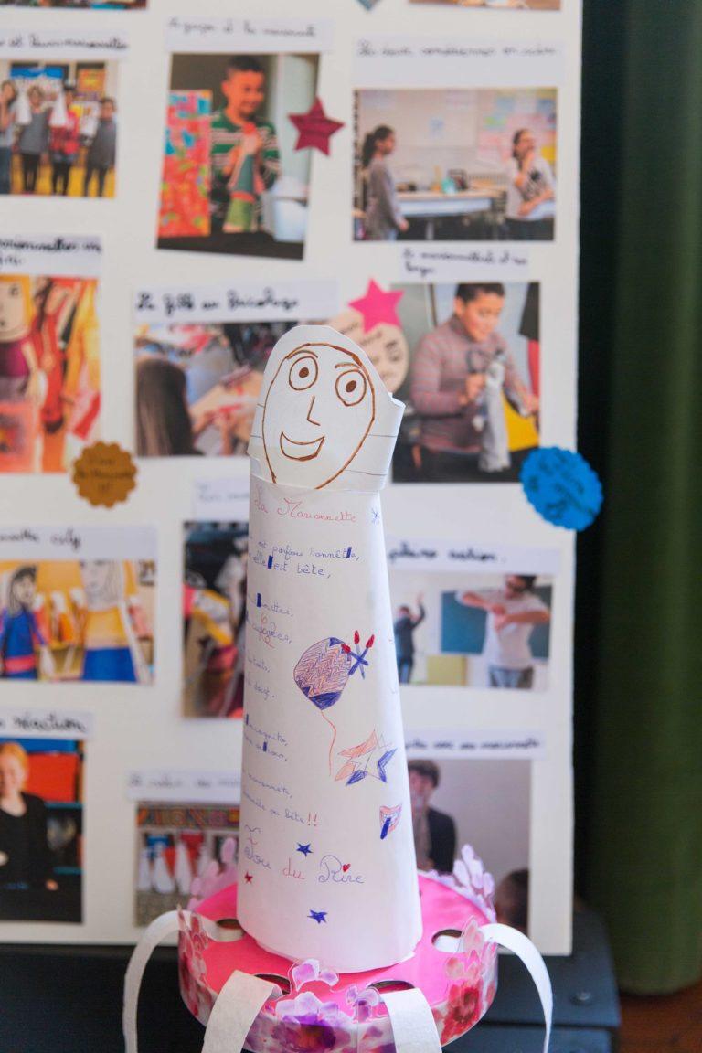 Au premier plan, un poème, une ode à la marionnette improvisée par une élève enjouée, devenu une marionnette à son tour.