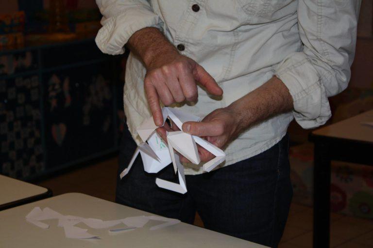 Stéphane Gantelet nous montre sur un patron vierge de décoration comment on plie et on restructure l'ensemble, bord à bord grâce aux languettes de collage.